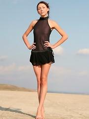 Tall skinny brunette taking off her transparent black dress on the beach