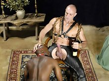 Sitting in a chair like a throne is super macho Daddy Luc Lemaitre and his impressive cock. At his feet, is Dark Skin, a hot black man wearing a colla
