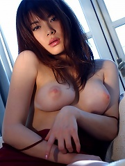 Japanese girl in red lingerie poses on the couch and slowly strips out of her clothes and lies back to show off her milky white tits.