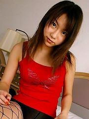Cute Japanese teen in fishnet stockings plays with her feet and shows upskirts before exposing her hard nips.