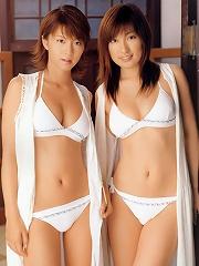 Two sensuous asian babes posing together in their white bikinis
